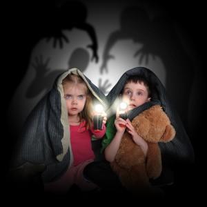 Fear of two children hiding under blanket.