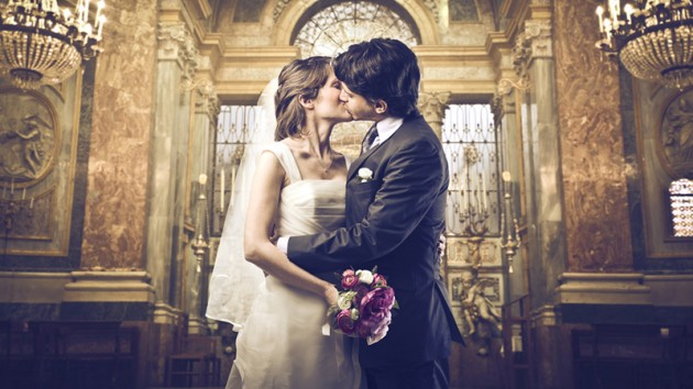 Newlyweds kissing in front of altar.