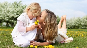 Mother kissing her daughter in the park.