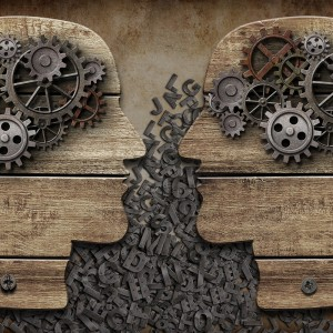Communication concept with gears and wooden heads.