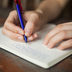 Writing in a notebook.